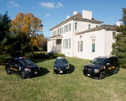 Three Park Police vehicles on display parked on a lawn in front home.