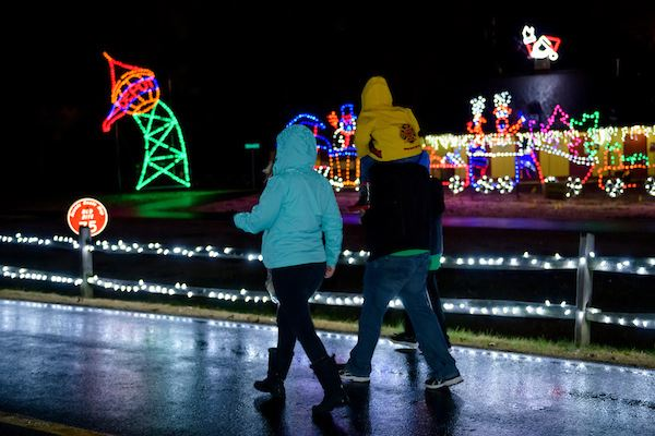 A family walking outdoors at night with bright holiday lights lit up behind them