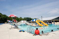 View of the pool with two yellow water slides at Allentown Splash Park on a sunny day