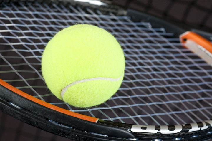 close up of tennis ball on racquet