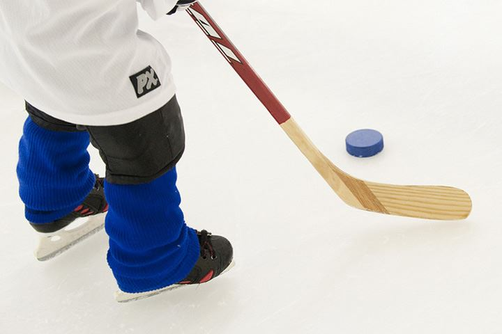 Closeup of ice hockey player using their hockey stick to push the puck on ice