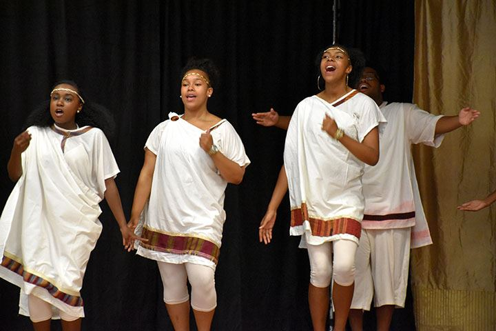 Four teens singing onstage in traditional Greek fashion