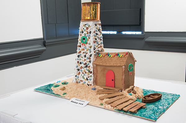 A gingerbread house designed as a lighthouse with a candy beach and boat out front