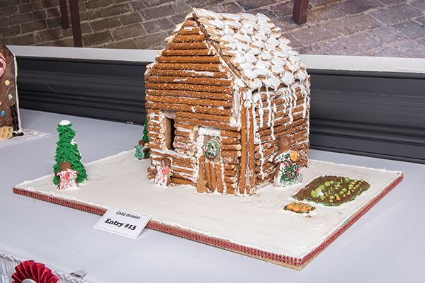 A gingerbread house decorated with pretzel sticks and icing