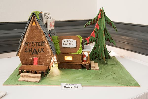 "A gingerbread house with ""Mystery Shack"" written above the doorway"
